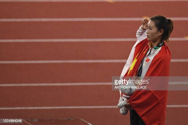 Gold medallist China's Yang Jiayu salutes during the victory ceremony for the women's 20km race walk athletics event during the 2018 Asian Games in...