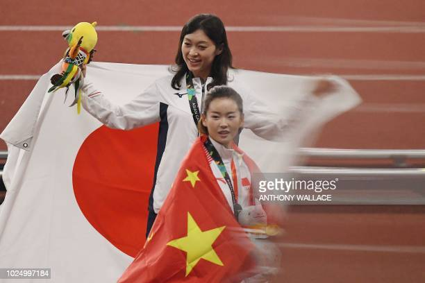 Gold medallist China's Yang Jiayu walks past bronze medallist Japan's Kumiko Okada during the victory ceremony for the women's 20km race walk...