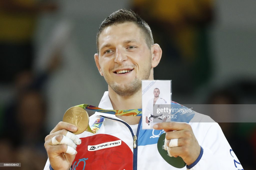 TOPSHOT - Gold medallist Czech Republic's Lukas Krpalek celebrates on the podium of the men's -100kg judo contest of the Rio 2016 Olympic Games in Rio de Janeiro on August 11, 2016. / AFP PHOTO / Jack GUEZ