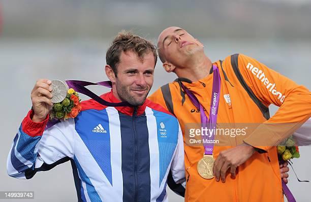 Gold medallist Dorian Van Rijsselberge of Netherlands celebrates with silver medallist Nick Dempsey of Great Britain following the Men's RSX Sailing...