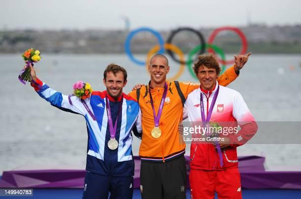 Gold medallist Dorian Van Rijsselberge of Netherlands celebrates with silver medallist Nick Dempsey of Great Britain and bronze medallist Przemyslaw...