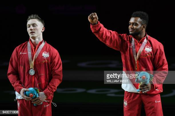 Gold medallist England's Courtney Tulloch gestures beside silver medallist and compatriot Nile Wilson after the men's rings final artistic gymnastics...