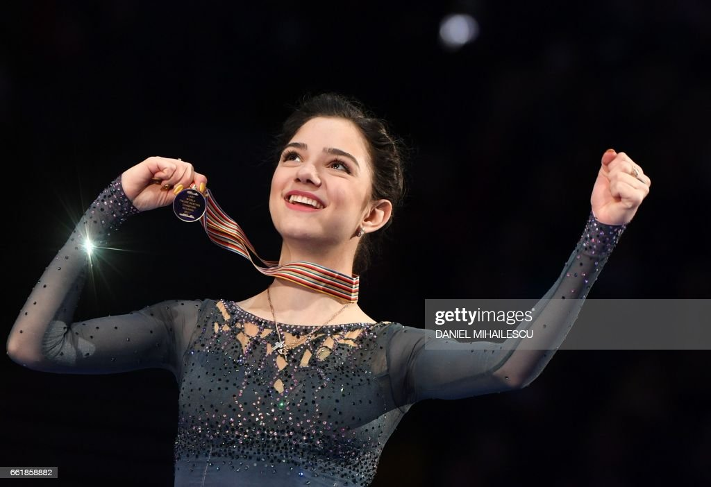 TOPSHOT - Gold medallist Evgenia Medvedeva of Russia celebrates with her medal on the podium after the woman's Free Skating event at the ISU World Figure Skating Championships in Helsinki, Finland on March 31, 2017. Evgenia Medvedeva of Russia won the Gold medal ahead of Silver medallist Canada's Kaetlyn Osmond and Bronze medallist Canada's Gabrielle Daleman. / AFP PHOTO / Daniel MIHAILESCU