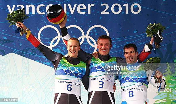 Gold medallist Felix Loch of Germany celebrates with silver medallist David Moeller of Germany and bronze medallist Armin Zoeggeler of Italy after...