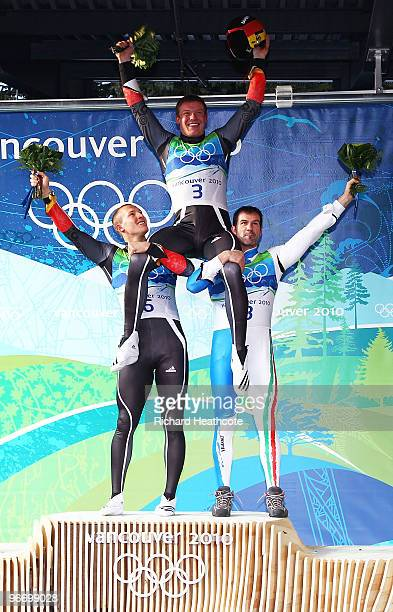 Gold medallist Felix Loch of Germany is held aloft by silver medallist David Moeller of Germany and bronze medallist Armin Zoeggeler of Italy after...