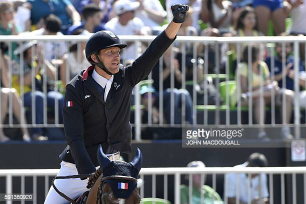 Gold medallist France's Kevin Staut riding Reveur de Hurtebise reacts during the jumping competition at the Olympic Equestrian Centre during the Rio...