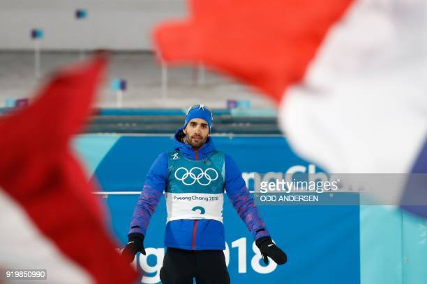 TOPSHOT Gold medallist France's Martin Fourcade celebrates on the podium during the victory ceremony in the men's 15km mass start biathlon event...