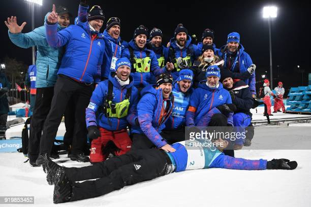 TOPSHOT Gold medallist France's Martin Fourcade celebrates with his team following the victory ceremony in the men's 15km mass start biathlon event...