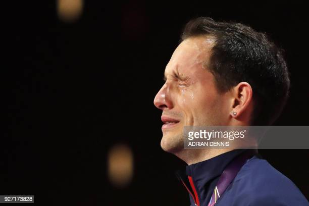 TOPSHOT Gold medallist France's Renaud Lavillenie reacts on the podium during the medal ceremony for the men's pole vault at the 2018 IAAF World...