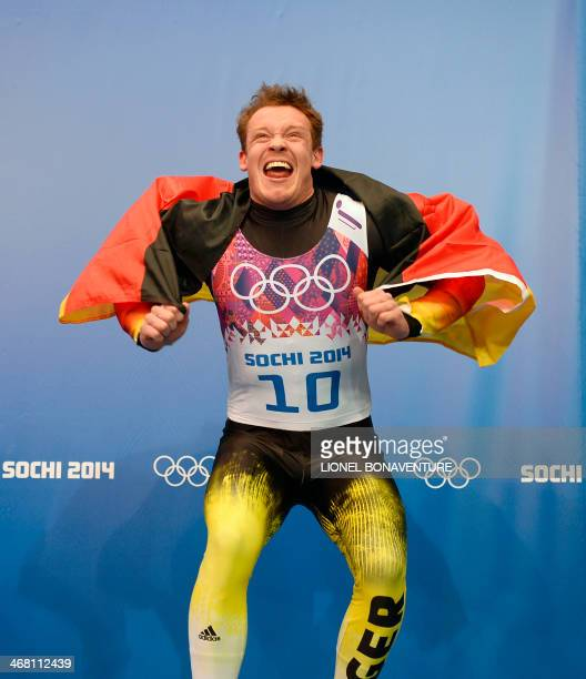 Gold Medallist Germany's Felix Loch celebrates on the podium at the Men's Luge Singles Flower Ceremony at the Sanki Sliding Center during the Sochi...