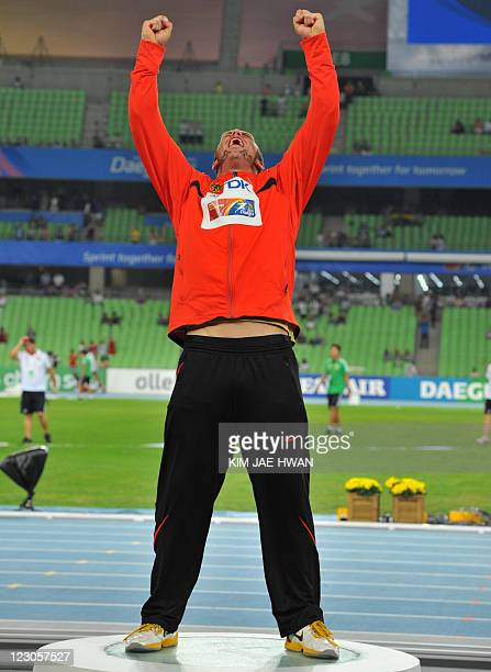 Gold medallist Germany's Robert Harting celebrates on the podium during the award ceremony for the men's discus throw event at the International...