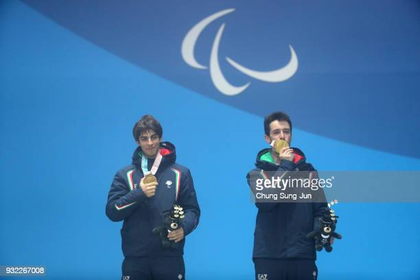 Gold medallist Giacomo Bertagnolli of Italy and his guide Fabrizio Casal celebrate on the podium during the medal ceremony for Alpien Skiing Men's...