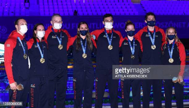 Gold medallist Great Britain's men and women team members pose after the final of the Womens 4x100m Medley Relay Swimming event during the LEN...