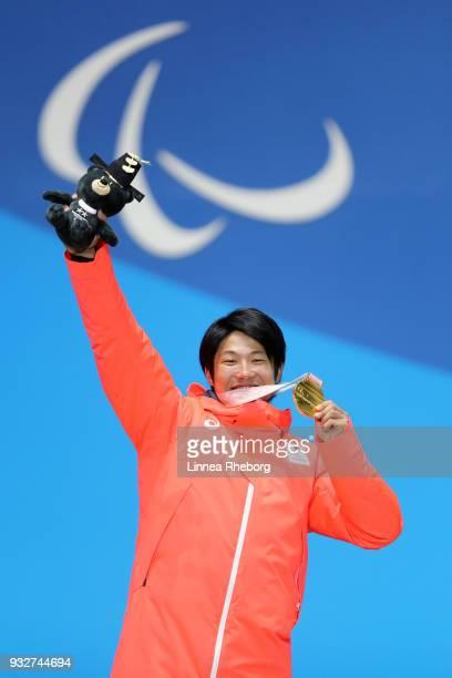Gold medallist Gurimu Narita of Japan celebrates during the medal ceremony for the Men's Snowboard Banked Slalom SBLL2 Finalduring the Biathlon on...