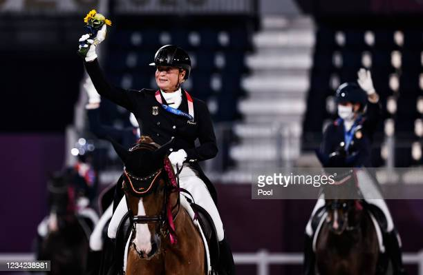 Gold medallist Isabell Werth of Germany rides on her horse together with other medallists after the medal ceremony on day four of the Tokyo 2020...