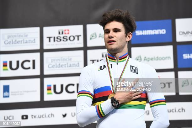 Gold medallist Italy's Filippo Ganna celebrates on the podium after the men's individual pursuit race final during the UCI Track Cycling World...
