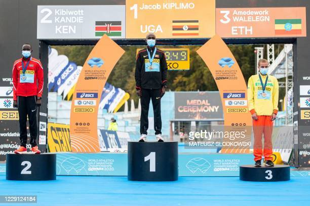 Gold medallist Jacob Kiplimo of Uganda poses on the podium next to silver medallist Kibiwott Kandie of Kenya and Amedework Walelegn of Ethiopia after...
