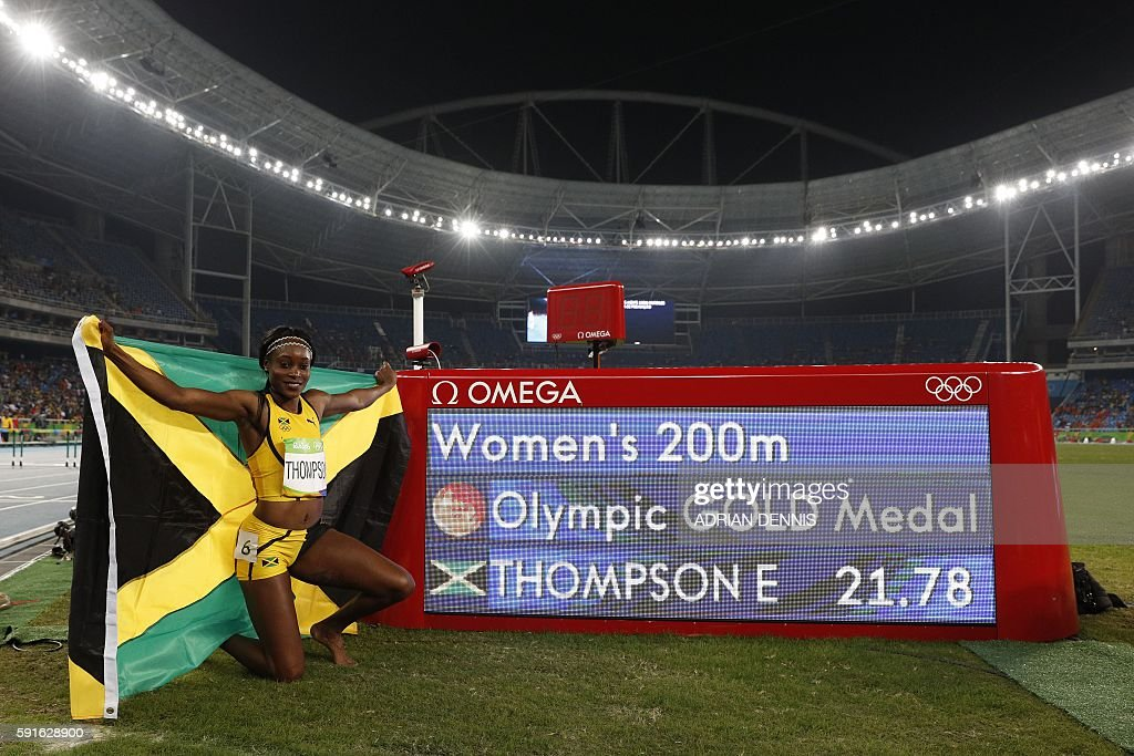 Gold medallist Jamaica's Elaine Thompson celebrates winning the Women's 200m Final during the athletics event at the Rio 2016 Olympic Games at the Olympic Stadium in Rio de Janeiro on August 17, 2016. / AFP / Adrian DENNIS