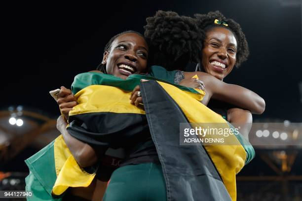 Gold medallist Jamaica's Kimberly Williams and teammate silver medallist Shanieka Ricketts hug bronze medallist Dominica's Thea Lafond after the...