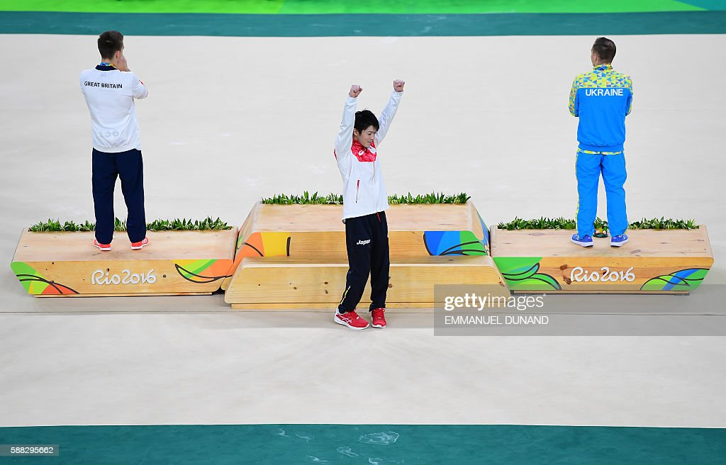 TOPSHOT - Gold medallist Japan's Kohei Uchimura (C) celebrates next to silver medallist Ukraine's Oleg Verniaiev (R) and bronze medallist Britain's Max Whitlock on the podium of the men's individual all-around final of the Artistic Gymnastics at the Olympic Arena during the Rio 2016 Olympic Games in Rio de Janeiro on August 10, 2016. / AFP / EMMANUEL