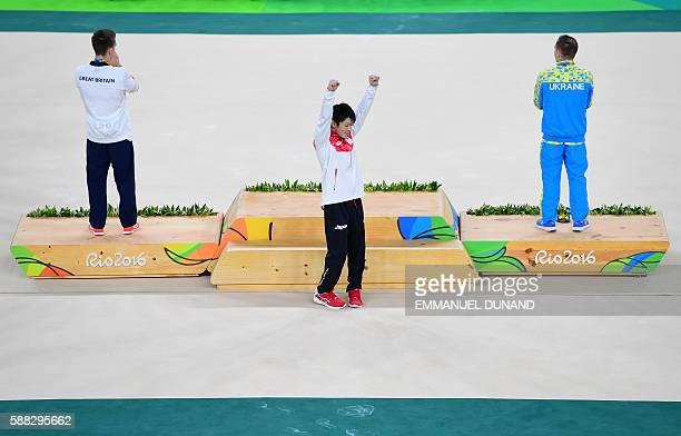 TOPSHOT Gold medallist Japan's Kohei Uchimura celebrates next to silver medallist Ukraine's Oleg Verniaiev and bronze medallist Britain's Max...