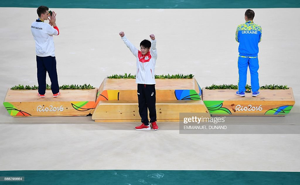 Gold medallist Japan's Kohei Uchimura (C) celebrates next to silver medallist Ukraine's Oleg Verniaiev (R) and bronze medallist Britain's Max Whitlock on the podium of the men's individual all-around final of the Artistic Gymnastics at the Olympic Arena during the Rio 2016 Olympic Games in Rio de Janeiro on August 10, 2016. / AFP / EMMANUEL