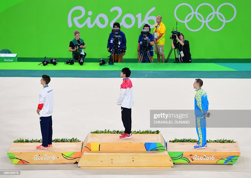 Gold medallist Japan's Kohei Uchimura (C), silver medallist Ukraine's Oleg Verniaiev (R) and bronze medallist Britain's Max Whitlock listen to the Japanese national anthem on the podium of the men's individual all-around final of the Artistic Gymnastics at the Olympic Arena during the Rio 2016 Olympic Games in Rio de Janeiro on August 10, 2016. / AFP / EMMANUEL