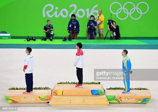 Gold medallist Japan's Kohei Uchimura , silver medallist Ukraine's Oleg Verniaiev and bronze medallist Britain's Max Whitlock listen to the Japanese...