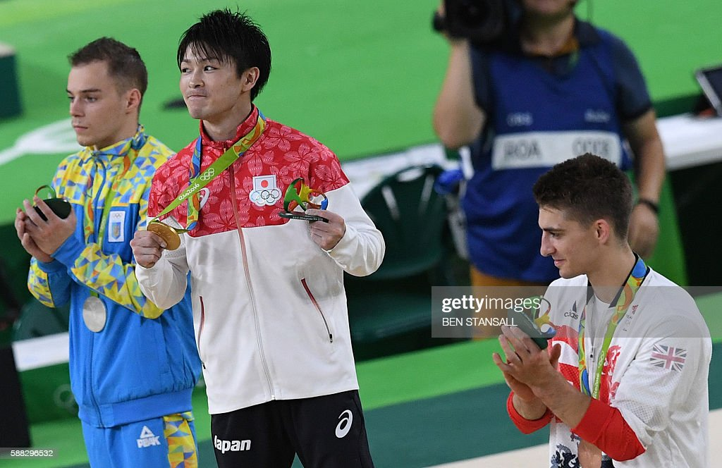 Gold medallist Japan's Kohei Uchimura (C), silver medallist Ukraine's Oleg Verniaiev (L) and bronze medallist Britain's Max Whitlock pose on the podium of the men's individual all-around final of the Artistic Gymnastics at the Olympic Arena during the Rio 2016 Olympic Games in Rio de Janeiro on August 10, 2016. / AFP / Ben STANSALL