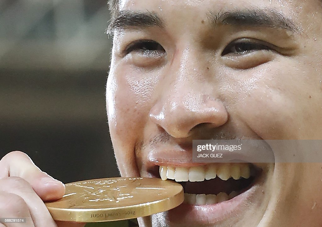 Gold medallist Japan's Mashu Baker celebrates on the podium of the men's -90kg judo contest of the Rio 2016 Olympic Games in Rio de Janeiro on August 10, 2016. / AFP / Jack GUEZ