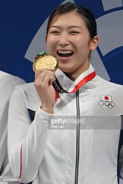 Gold medallist Japan's Rikako Ikee celebrates during the victory ceremony of the women's 100m freestyle swimming event during the 2018 Asian Games in...