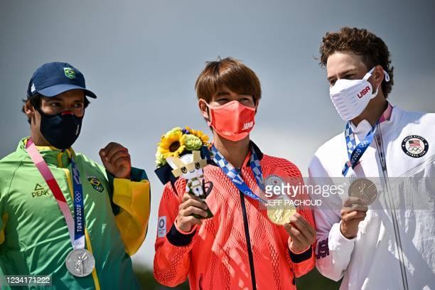 Gold medallist Japan's Yuto Horigome , silver medallist Brazil's Kelvin Hoefler and bronze medallist Jagger Eaton of the US pose on the podium at the...