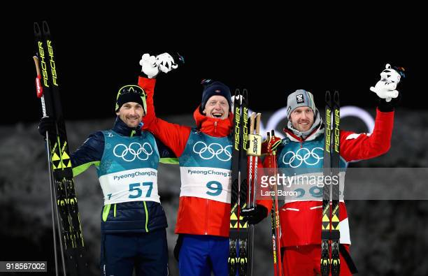 Gold medallist Johannes Thingnes Boe of Norway celebrates with silver medallist Jakov Fak of Slovenia and bronze medallist Dominik Landertinger of...