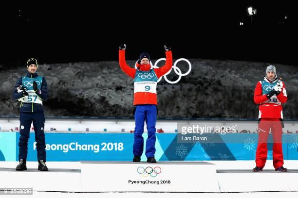 Gold medallist Johannes Thingnes Boe of Norway celebrates with silver medallist Jakov Fak of Slovenia and bronze medallist Dominik Landertinger of...