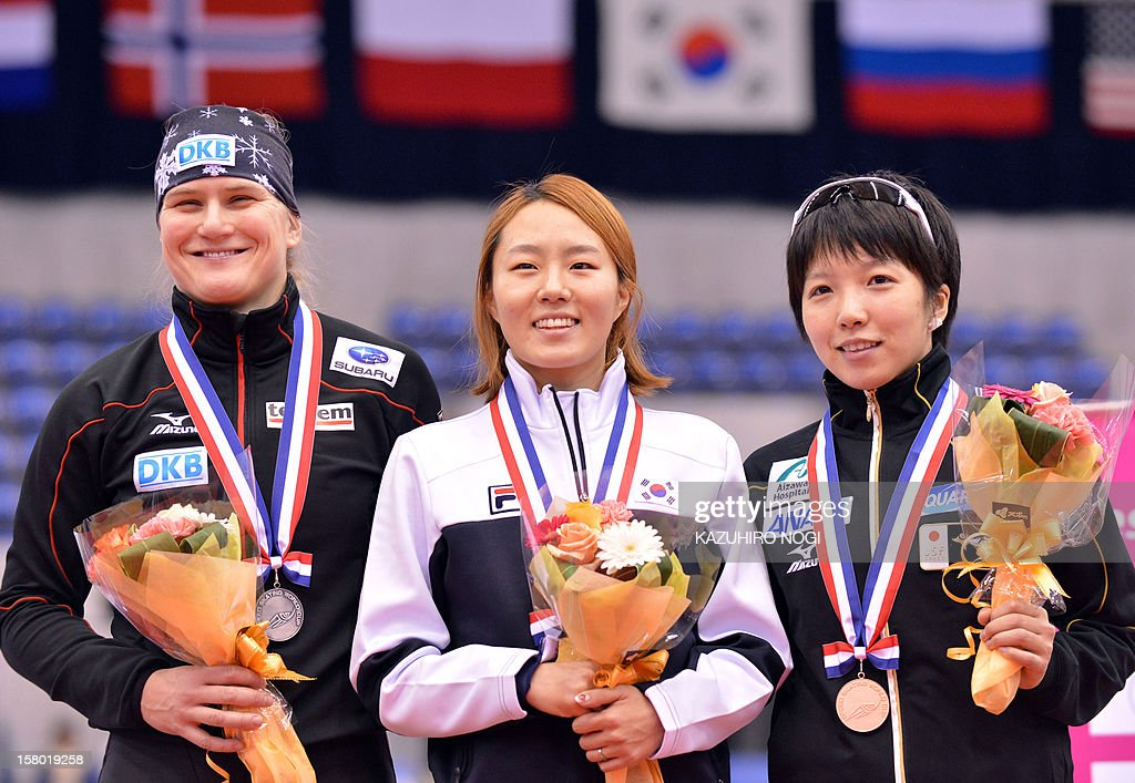 Gold medallist Lee Sang-Hwa of South Korea (C), silver medallist Jenny Wolf of Germany (L) and bronze medallist Nao Kodaira of Japan (R) celebrate on the podium during the awards ceremony for the women's 500 meters competition at the World Cup speed skating event at the Nagano M-Wave ice arena on December 9, 2012.