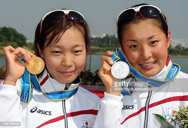 Gold medallist Mariko Adachi of Japan poses for a picture with fellow silver medalist Akane Tsuchihashi after winning the woman's triathlon...