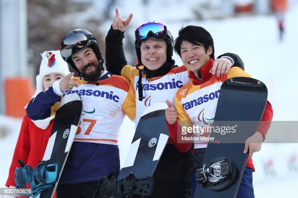 Gold medallist Matti SuurHamari of Finland celebrates with Silver medallist Keith Gabel of USA and Gurimu Narita of Japan in the Men's Snowboard...