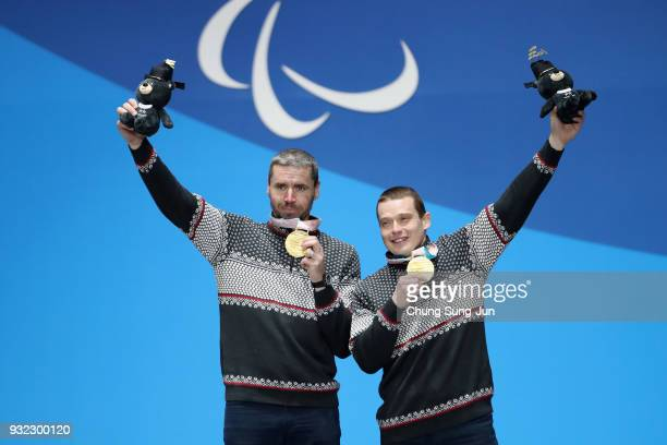 Gold medallist Miroslav Haraus of Slovakia and guide Maros Hudik celebrate on the podium during the medal ceremony for the Alpien Skiing Men's Super...