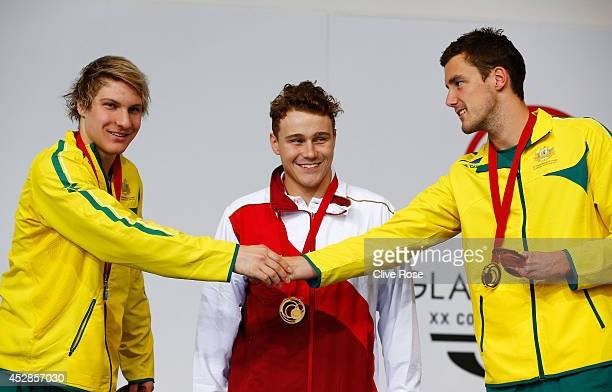 Gold medallist Oliver Hynd of England looks on as silver medallist Jesse Aungles of Australia shakes hands with bronze medallist Blake Cochrane of...