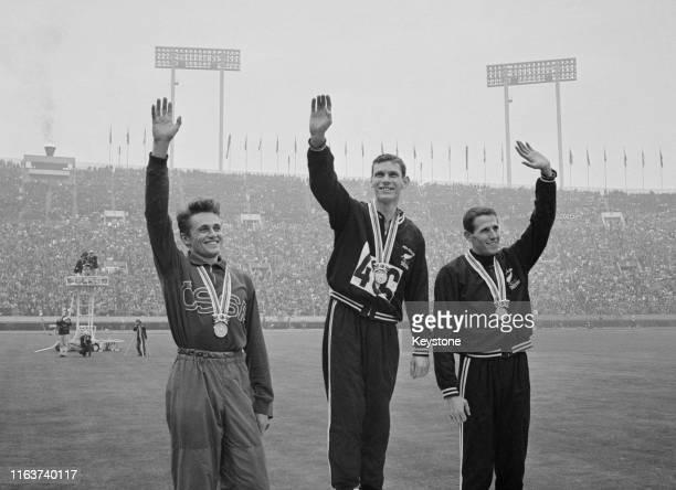 Gold medallist Peter Snell of New Zealand celebrates with silver medallist Josef Odlozil of Czechoslovakia and bronze medal winning compatriot John...