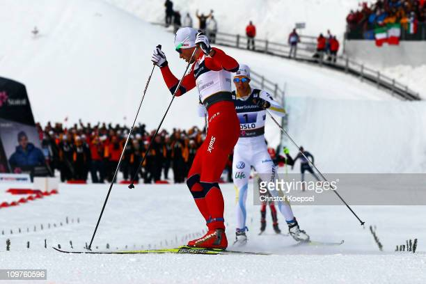 Gold Medallist Petter Northug of Norway stops prior to the line as if to taunt silver medallist Marcus Hellner of Sweden in the Men's Cross Country...