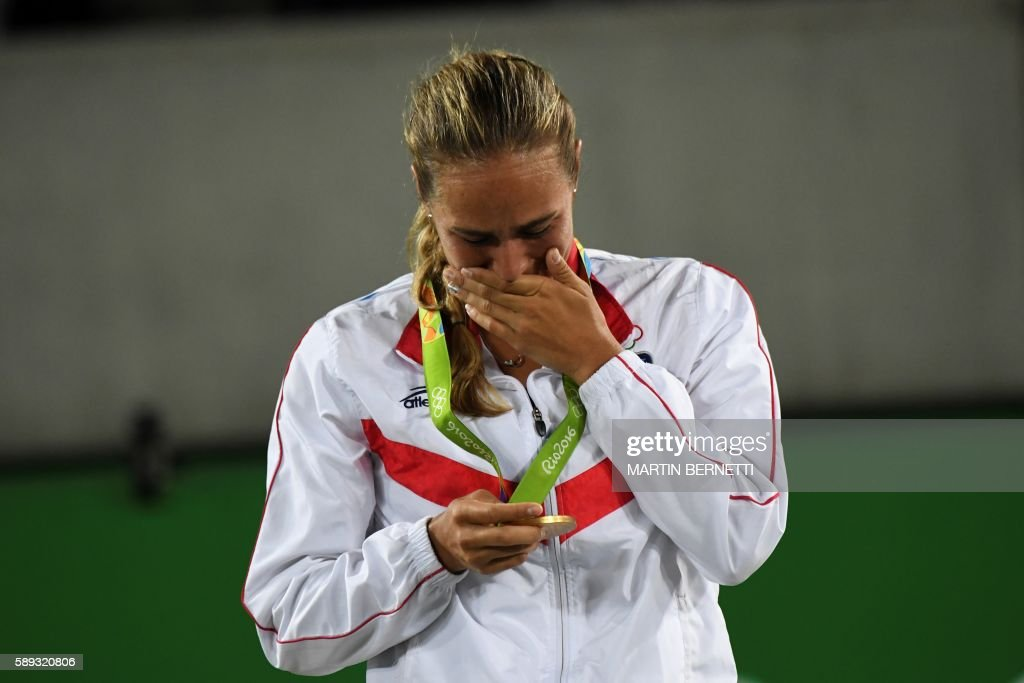 TOPSHOT - Gold medallist Puerto Rico's Monica Puig reacts during the podium ceremony of the women's singles tennis event at the Olympic Tennis Centre of the Rio 2016 Olympic Games in Rio de Janeiro on August 13, 2016. / AFP PHOTO / Martin BERNETTI