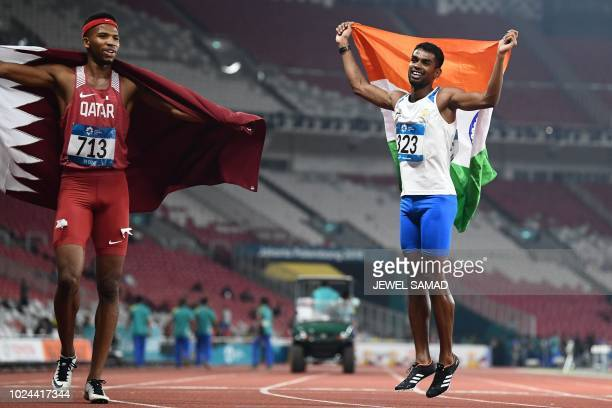 Gold medallist Qatar's Abderrahman Samba and silver medallist India's Dharun Ayyasamy celebrate after the final of the men's 400m hurdles athletics...