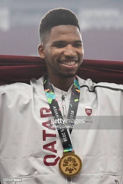 Gold medallist Qatar's Abderrahman Samba celebrates during the victory ceremony for the men's 400m hurdles athletics event during the 2018 Asian...