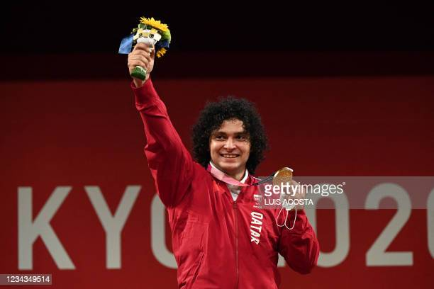 Gold medallist Qatar's Fares Ibrahim E H Elbakh poses on the podium for the victory ceremony of the men's 96kg weightlifting competition during the...