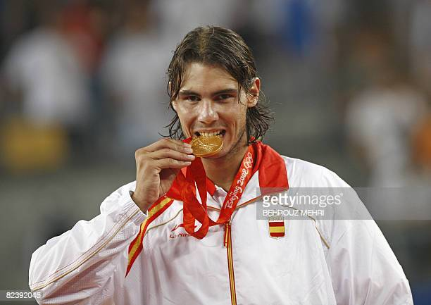 Gold medallist Rafael Nadal of Spain bites his gold medal while posing on the podium during the awards ceremony following Nadal's victory over...
