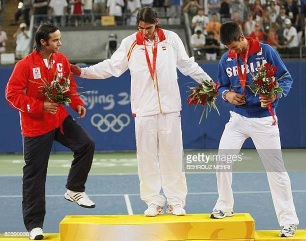 Gold medallist Rafael Nadal of Spain gestures to silver medallist Fernando Gonzalez of Chile and bronze medallist Noval Djokovic of Serbia to pose...