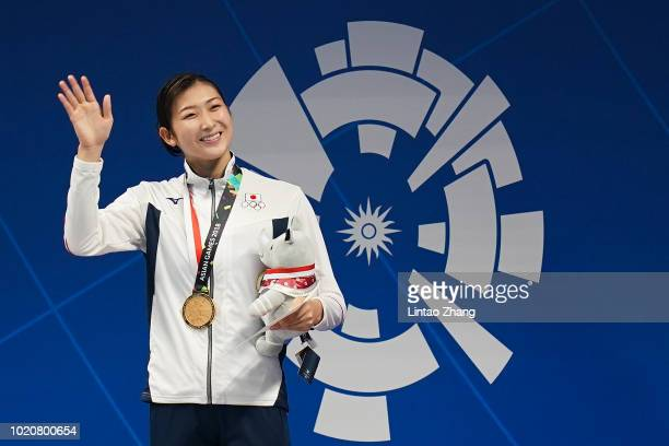 Gold medallist Rikako Ikee of Japan celebrate during the victory ceremony for the women's 100m butterfly swimming event on day three of the Asian...