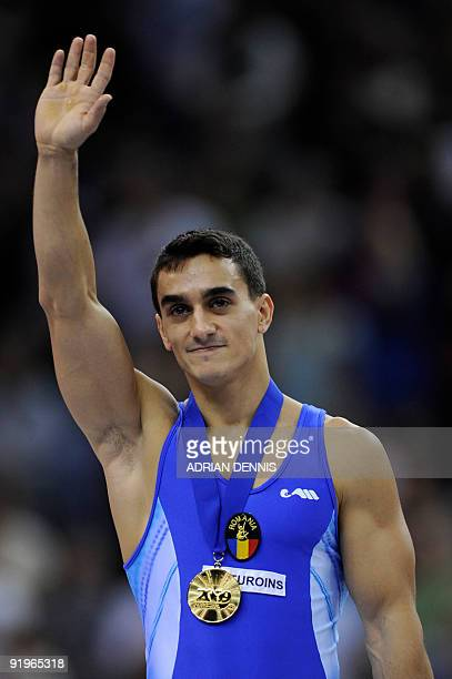 Gold medallist Romania's Marian Dragulescu poses for photographs after winning the men's floor event in the apparatus finals during the Artistic...