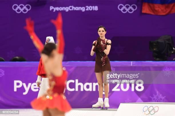 Gold medallist Russia's Alina Zagitova celebrates as silver medallist Russia's Evgenia Medvedeva claps before the venue ceremony after the women's...